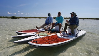 Flyfishermen having lunch on stand up paddle boards.